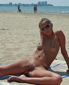 lustful young nudists sunbathes fully naked at beach among men